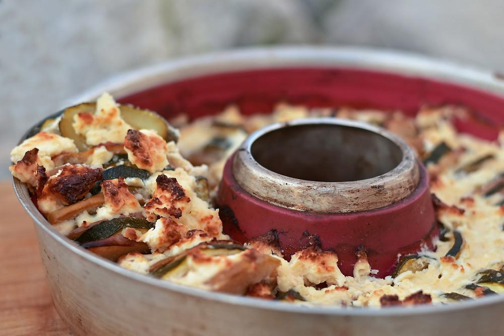 Vollkorn-Tomatenbrot aus dem Campingbackofen Omnia auf einem Holzbrett serviert.