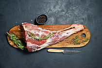 Raw leg of lamb on a wooden chopping Boa