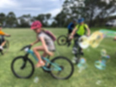 Kids having fun riding mountain bikes and popping bubbles