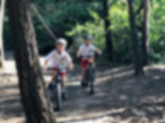 Two boys riding mountain bike trail.jpg