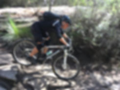 Male mountain biker rolling down rocks in a beginner clinic at Manly Dam