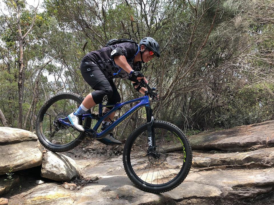 Woman riding mountain bike rocky trail