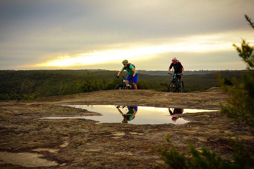 Man and woman mountain biking at sunset at Red Hill in Cromer NSW