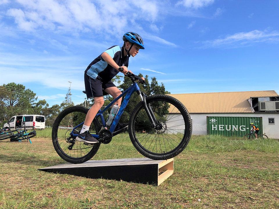 boy riding mountain bike over wooden ram