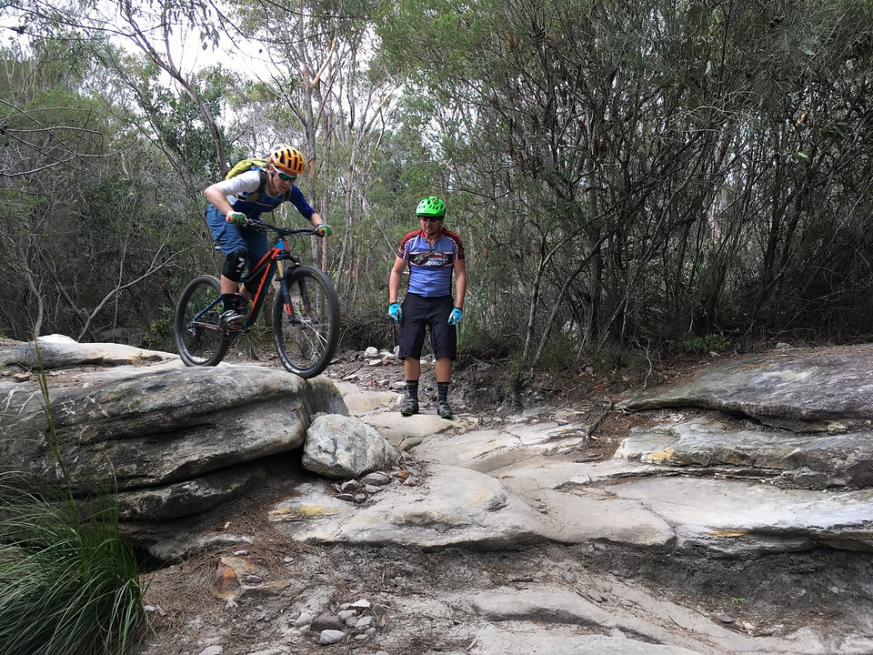 Female mountain biker rolling off rocks in lesson at Manly Dam