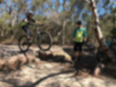 Young mountain biker riding off a drop in a mountain bike clinic for teenagers at Manly Dam