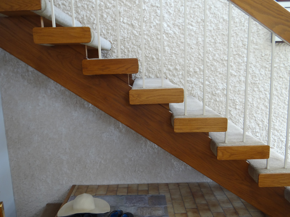 open rise stairs with stucco wall behind it