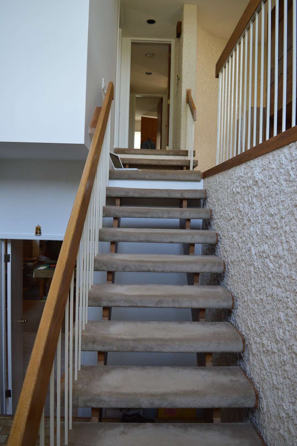 open riser stairs with stucco wall