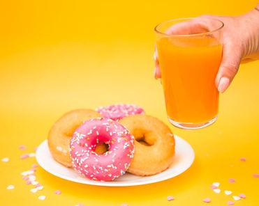 human-hand-holding-glass-juice-near-donu