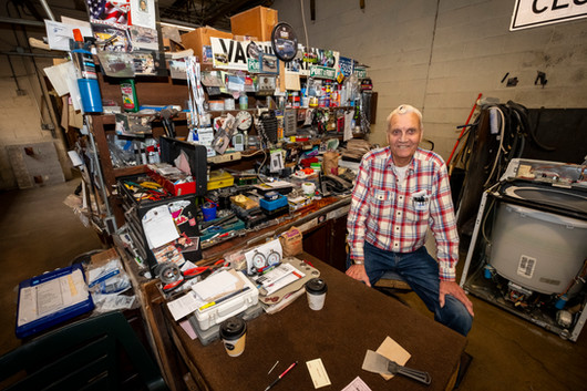 """In the back of Kimball Appliance in Port Huron, Vern """"Junebug"""" Norton, 79, sits in his workspace Thursday, June 13, 2019. Nick Bondarek, owner of the store, says some customers won't even look at new appliance because they would prefer a used appliance refurbished by Junebug.  Photographed on assignment for the Times Herald, June 2019."""