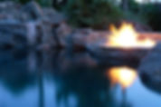 custom luxury pool with rocks and fire bowl fire featue