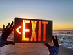Exit sign with sun at beach.PNG