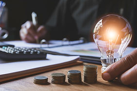 hand-male-holding-light-bulb-with-stack-