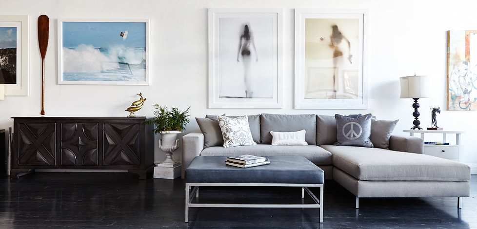 Image of the showroom, showcasing a modern grey sofa chaise with decorative throw pillows.