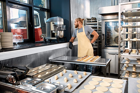 Young adult man working on kitchen in modern bakery factory with professional equipment, c