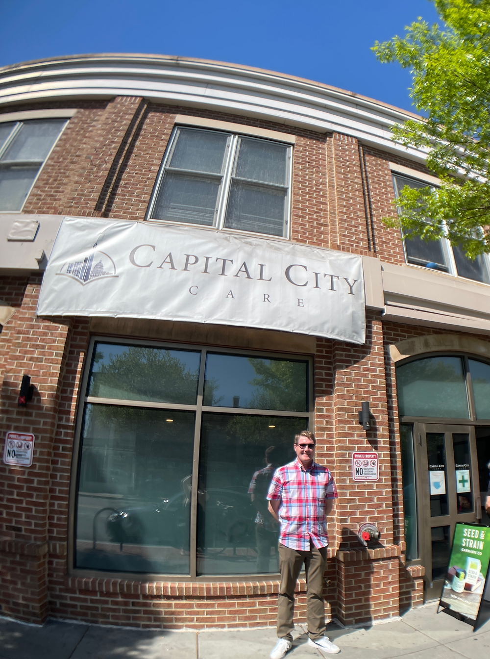 jack-dobbyn-of-tokers-guide-below-capital-city-care-sign-420-dc