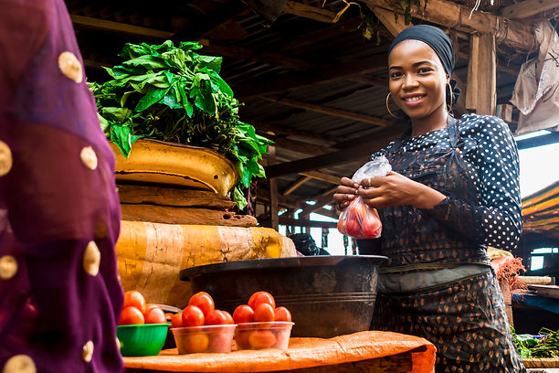 a girl selling tomatoes and vegetables i