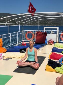 Yoga Teacher, Yogawithvickib, sitting in Lotus meditation on private boat in Kalkan Bay, Turkey