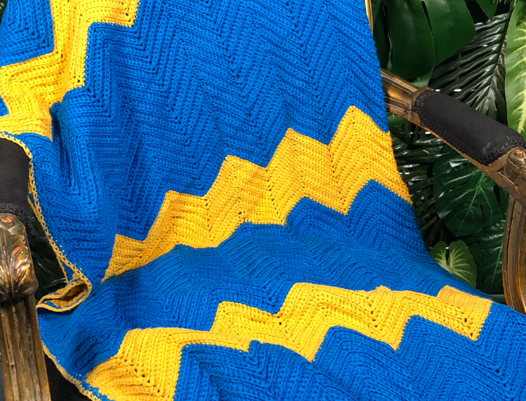 1980s hand knitted yellow and blue zig zag print blanket