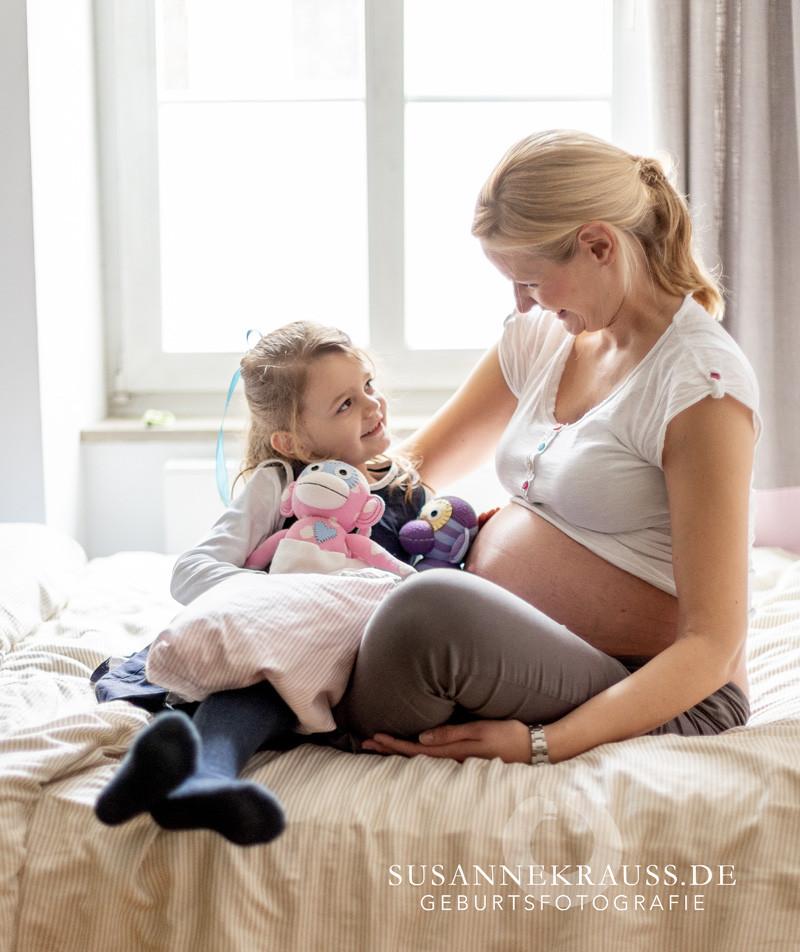 Schwangere Mama sitzt mit ihren Kind auf den Bett
