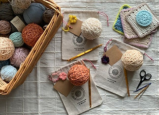 assortment of organic cotton yarn, handwound into balls. subtle muted shades of yarn. various crochet tools including hooks, scissors. handmade coasters and facial squares as samples.