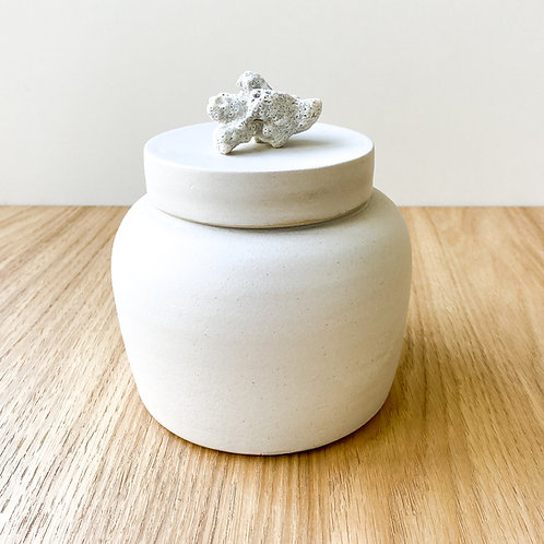 White jar with coral on lid