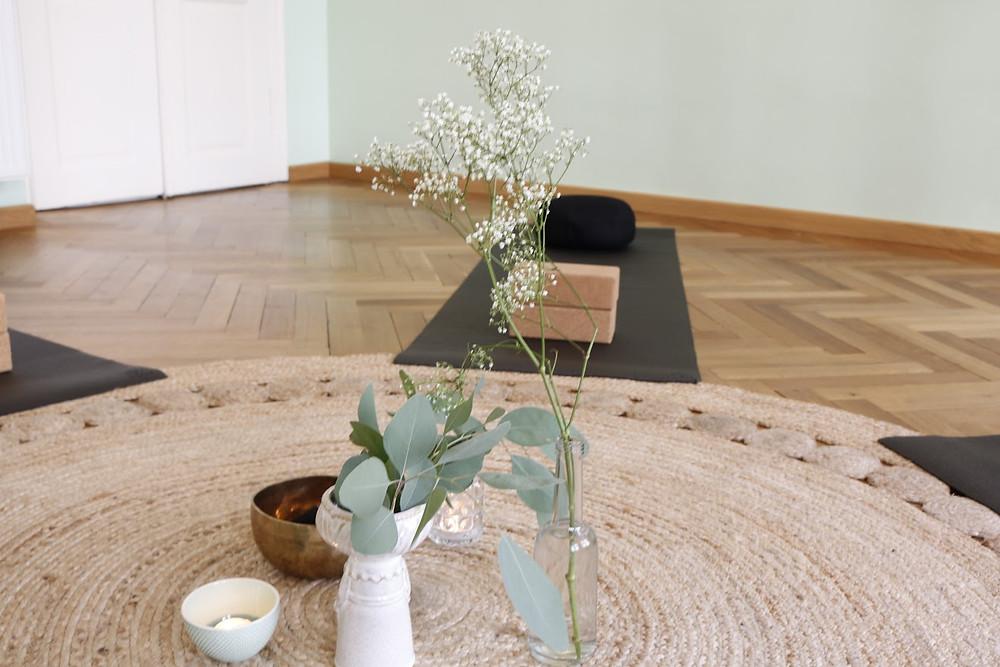Raum mit Holzboden, rundem Teppich und Yogamatten