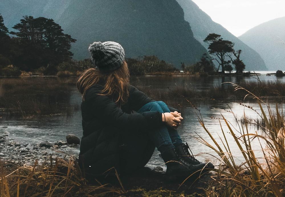 Eine Frau sitzt am See, Sie trägt Winterkleidung und blickt auf Berge, Wasser und Bäume. Sie sieht sehr nachdenklich aus.