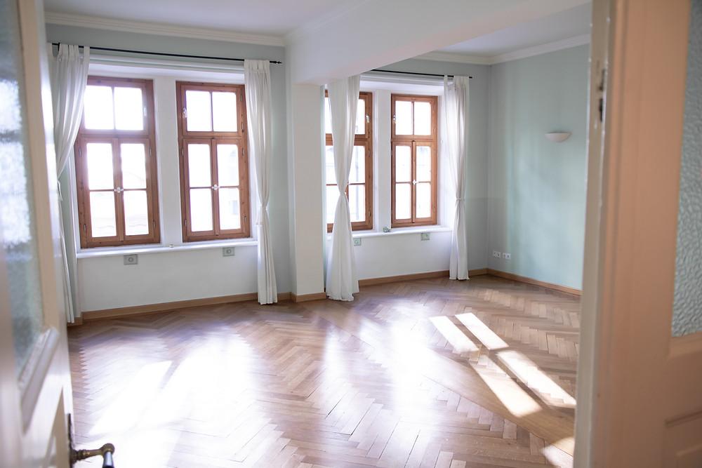 Heller Raum mit Fenstern und braunem Parkettboden
