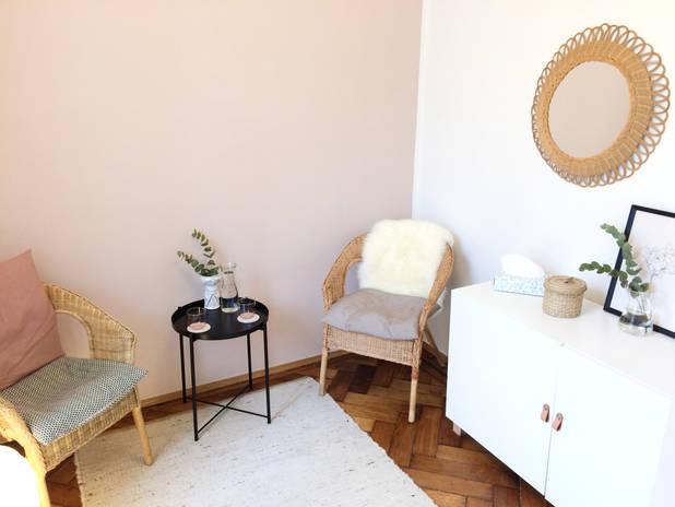 Behandlungsraum der Hypnosepraxis mit zwei Stühlen Teppich kleinem Tisch und Kommode
