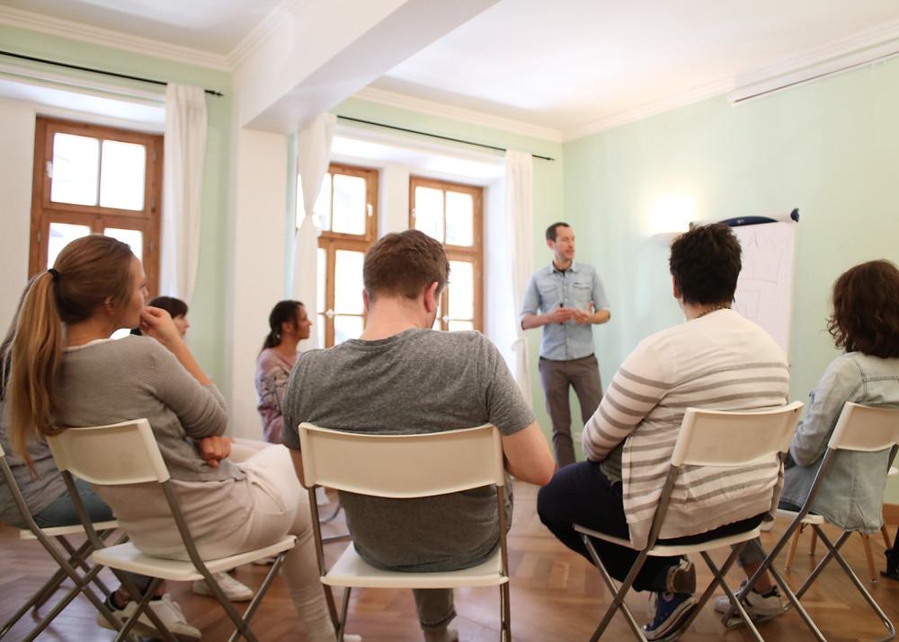 Ein Seminarraum mit türkisen Wänden. Stühle und Workshop-Teilnehmer. Ein Trainer mit Flipchart hält gerade ein Seminar ab.