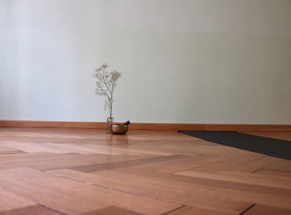 raum mit parkettboden und yoga matte