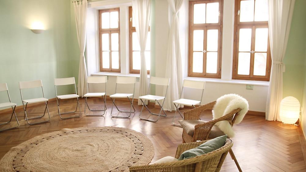 Raum mit türkisen Wänden und mehreren Stühlen, einem Teppich und einer Lampe in der Ecke. Der Raum ist hell und hat mehrere Fenster.