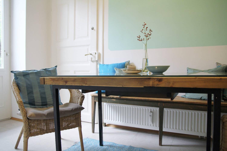 raum mit tisch, bank und einem stuhl