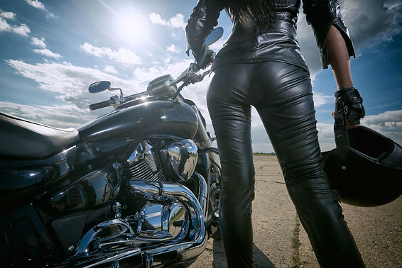 Biker girl in leather jacket standing by