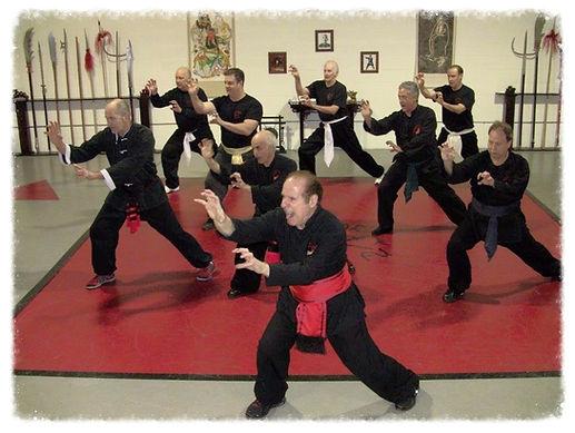 Man in red sash leading Kung Fu class in dojo