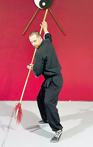Man in black sash in kung fu pose with bo staff in front of bo staffs and yin yang on wall