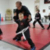 Teaching child in white belt kung fu