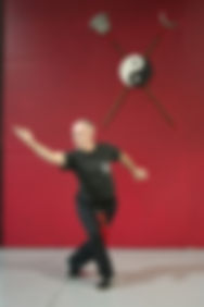 Man in black sash in kung fu pose in front of bo staffs and yin yang on wall