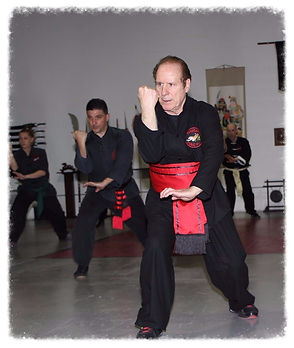 Man in Red Sash leading Kung Fu class practicing blocks