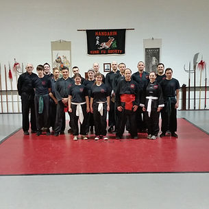 A group of Kung Fu students and master in various sashes