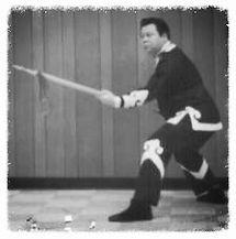 black and white image of Master Wong Ting Fong teaching rattan staff play kung fu