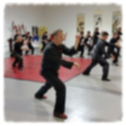 Class of adults practicing Kung Fu in a dojo