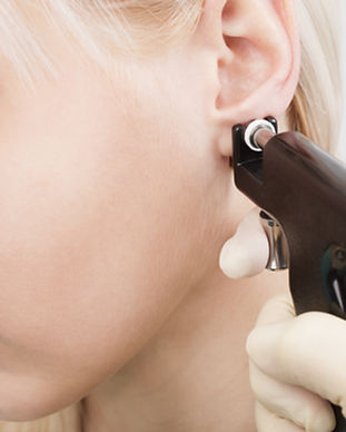 Woman having ear piercing process with s