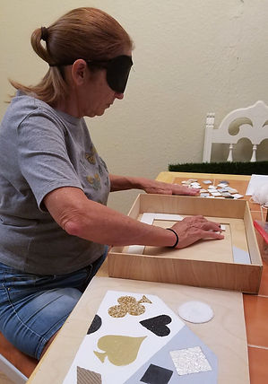 A woman on the left is blindfolded while playing the puzzle. She has multiple pieces of the puzzle, along with the box and lid sitting on the table in front of her. Her hands are placed far apart, feeling the pieces. In the background is a cream colored wall. The puzzle sits on an orange tiled table.