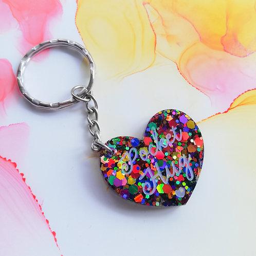 Handmade rainbow glitter resin pocket hug keyring on a card, heart keychain