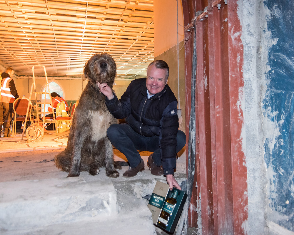 Cabra Castle MD Howard Corscadden and resident Irish wolfhound Oscar VI prepare to bury time capsule during final phase of €6m castle development . Image credit: Paul O'Callaghan Photography