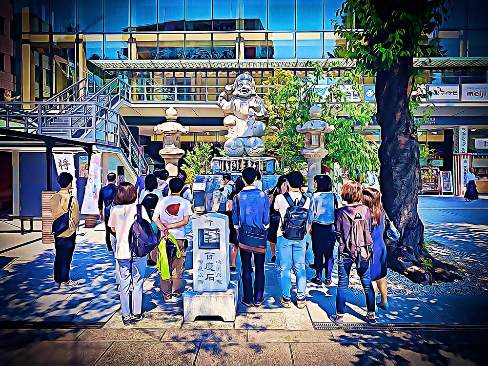 Group admiring the statue of Ebisu at Kanda Shrine, Chiyoda, Tokyo, Japan
