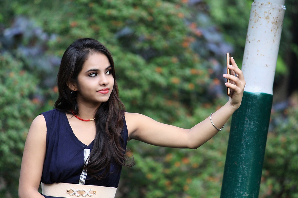 Pretty young Indian woman taking a selfie outside.