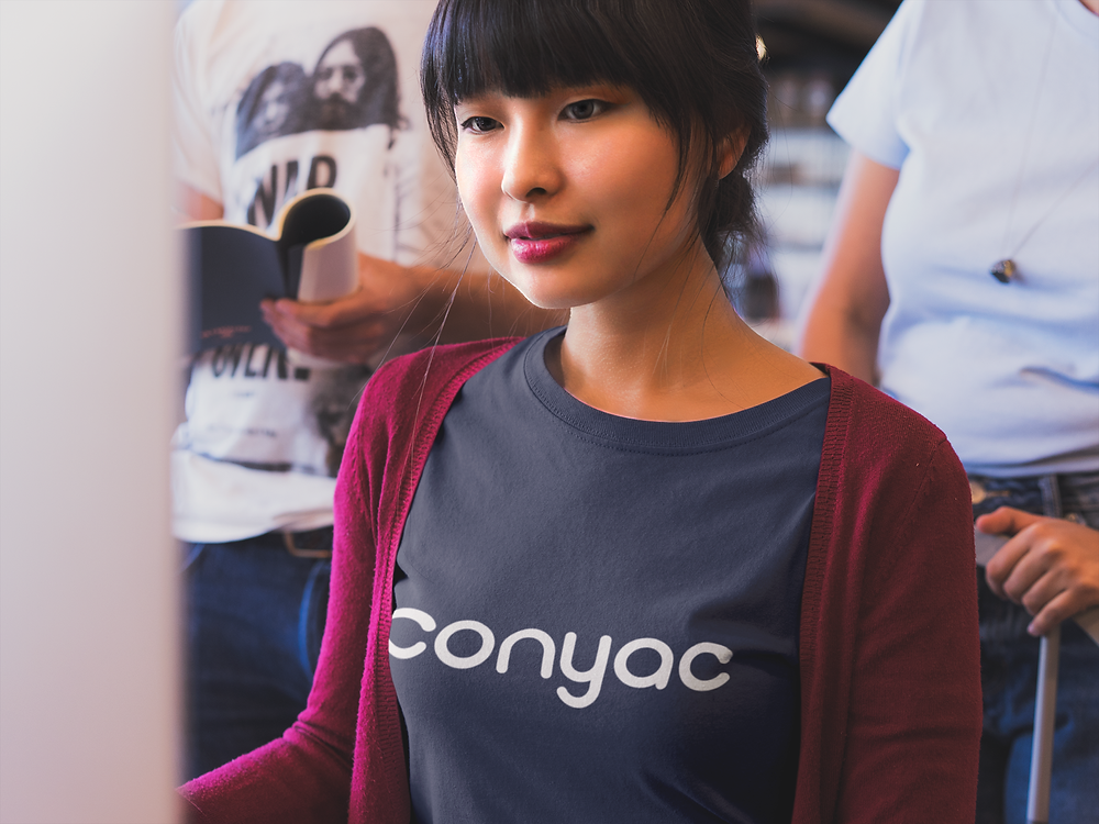Asian woman working in office with team wearing Conyac t-shirt